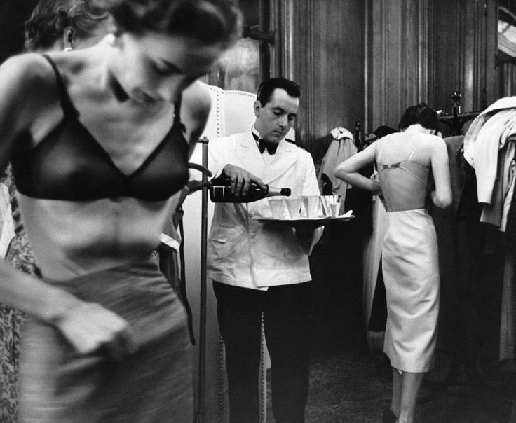 """""""Sahne Arkası"""" / """"backstage"""" Kurt Hutton - Picture Post - Getty Images Orijinal yayın / Original publication:Picture Post - 6434 - British Girls Storm Paris Yayım tarihi / Published: 1953 Fransa'daki bir de lede John Cavanagh'in mankenleri sahne arkasında üstlerini değiştirirken bir garson şampanya dolduruyor, 1953."""