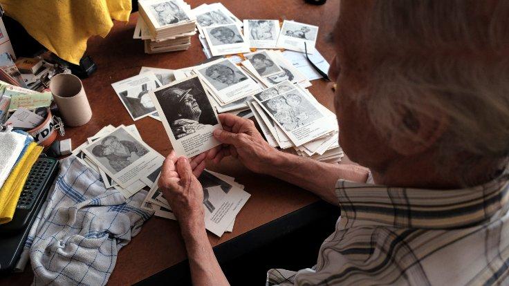 Ezilen insanların portlerini çizdiği kartpostallara bakarken...